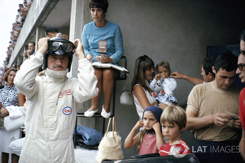 Graham Hill prepares for racing in pits, surrounded by his family: his wife Bette Hill and a nanny w