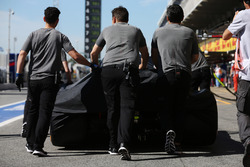 McLaren engineers move the car of Fernando Alonso, McLaren MCL32, in the pit lane, under covers