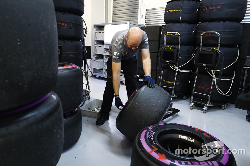 A McLaren engineer marks some tyres