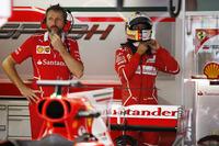 A Ferrari team member stands in front of Sebastian Vettel, Ferrari