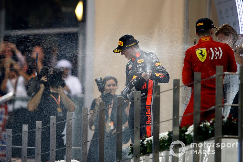 Max Verstappen, Red Bull Racing, 2nd position, Lewis Hamilton, Mercedes AMG F1, 1st position, and Charles Leclerc, Ferrari, 3rd position, spray Champagne on the podium