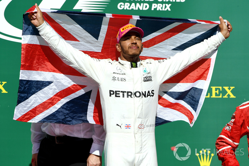 Race winner Lewis Hamilton, Mercedes AMG F1 celebrates on the podium with the Union Jack flag