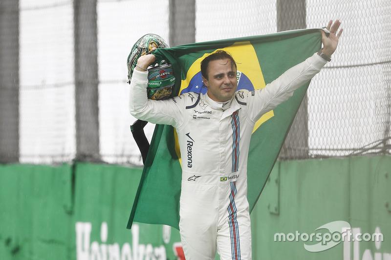 Felipe Massa, Williams, carries a Brazilian flag as he walks back to his garage in tears after crashing