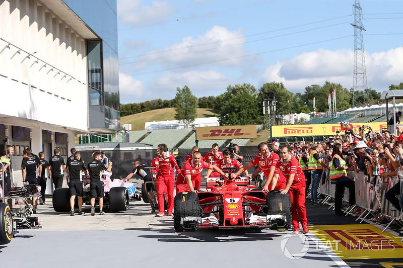 Mecánicos de Ferrari empujan el coche de Sebastian Vettel, Ferrari SF70-H