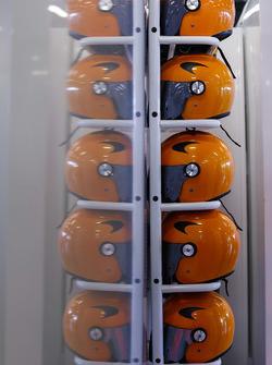 McLaren pit crew helmets on a rack