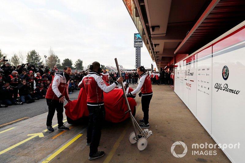Meccanici Alfa Romeo Racing con la nuova Alfa Romeo Racing C38, sotto al telo