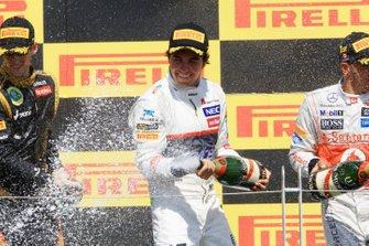 Romain Grosjean, Lotus F1 y Sergio Pérez, Sauber C31 celebran en el podio