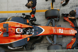 Stoffel Vandoorne, McLaren, is attended to by mechanics in the pit lane