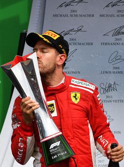 Il vincitore della gara Sebastian Vettel, Ferrari, festeggia sul podio e bacia il trofeo