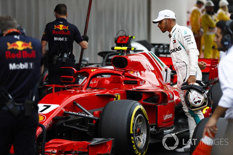 Обладатель поула гонщик Mercedes AMG F1 Льюис Хэмилтон изучает Ferrari SF71H Кими Райкконена