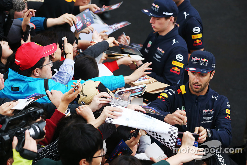 Daniel Ricciardo, Red Bull Racing, and Max Verstappen, Red Bull, sign autographs for fans