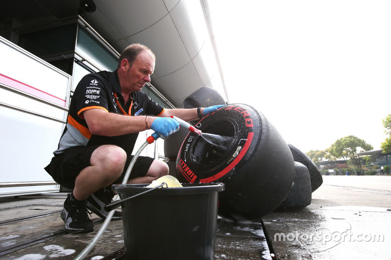 A Force India mechanic washes some Super Soft tyres and rims