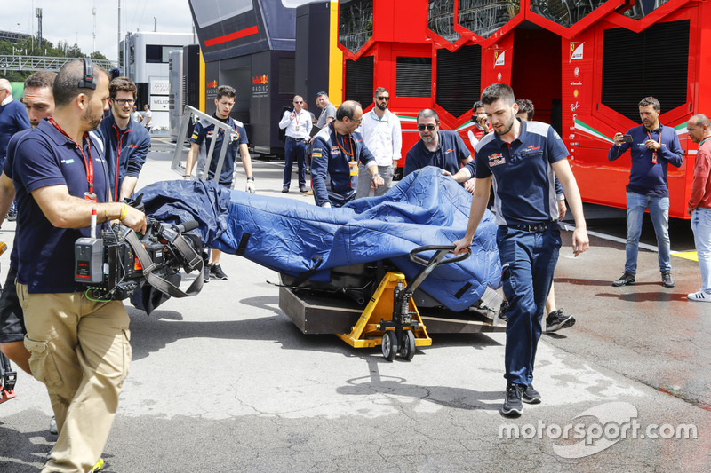 Scuderia Toro Rosso team members are filmed wheeling a monocoque under wraps through the paddock. Sky pundits Martin Brundle and David Croft look on