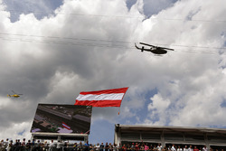 Вертолет проносит австрийский флаг над трибунами