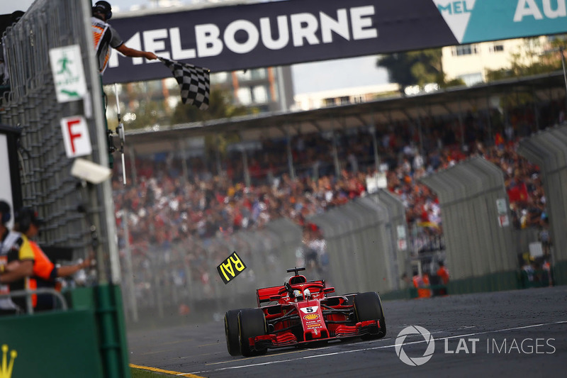 Sebastian Vettel, Ferrari SF71H, takes the chequered flag for victory as a piece of Ferrari pit boar