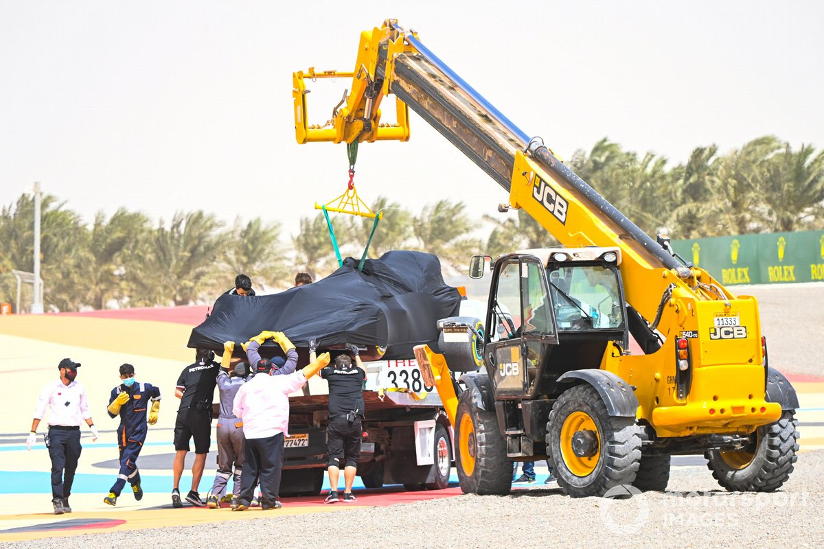 The car of Lewis Hamilton, Mercedes W12, is loaded onto a flat bed truck