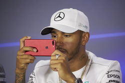 Lewis Hamilton, Mercedes AMG F1, uses his mobile phone in the press conference