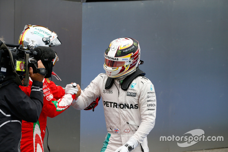 Переможець гонки Льюїс Хемілтон, Mercedes AMG F1 святкує в закритому парку разом з Себастьяном Феттелем, Ferrari