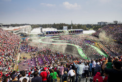 Fans watch the podium ceremony and invade the track