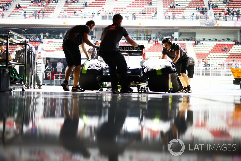 Mekanik memasukkan mobil Romain Grosjean, Haas F1 Team VF-18, ke garasi