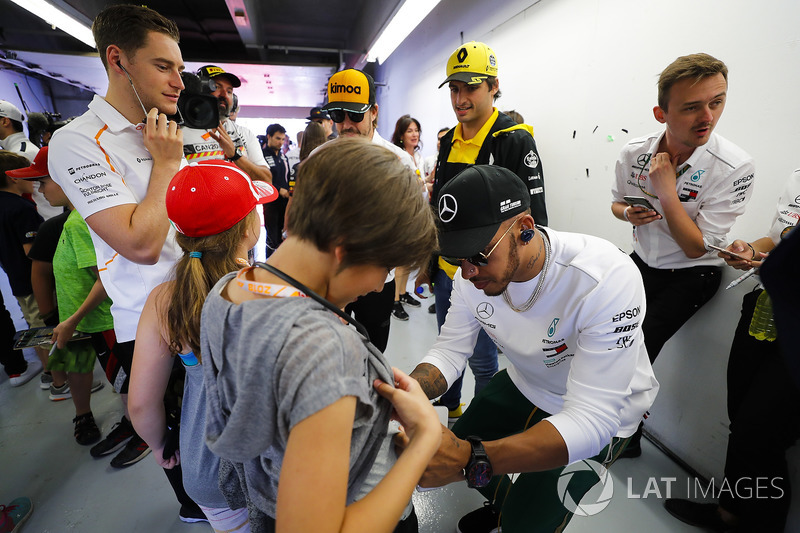 Lewis Hamilton, Mercedes AMG F1, signs a grid kid's short, as Carlos Sainz Jr., Renault Sport F1 Tea