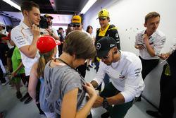 Lewis Hamilton, Mercedes AMG F1, signe le short d'un enfant sous les yeux de Carlos Sainz Jr., Renault Sport F1 Team, Fernando Alonso, McLaren et Stoffel Vandoorne, McLaren, look on