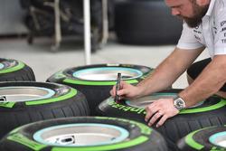 Un mécanicien Mercedes AMG F1 marque des pneus Pirelli