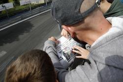 Spectator reading a newspaper with Joel Eriksson, Motopark Dallara F317 - Volkswagen