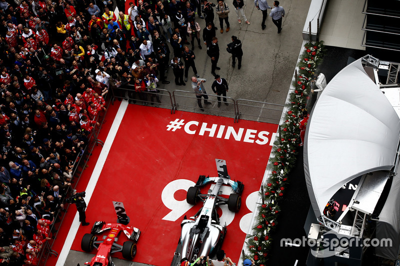 Lewis Hamilton, Mercedes AMG, and Sebastian Vettel, Ferrari, spray Champagne on the podium