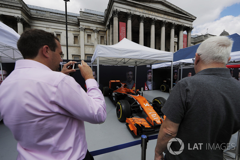 A fan takes a photo of the McLaren MCL32 on the teams stand