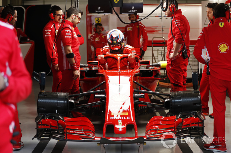 Kimi Raikkonen, Ferrari, enters his cockpit