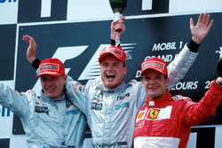 Podium: second place Mika Hakkinen, McLaren, race winner David Coulthard, McLaren, third place Rubens Barrichello, Ferrari