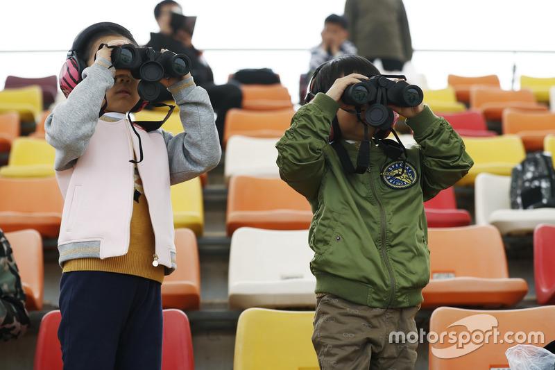 De jeunes fans regardent les F1 avec des jumelles