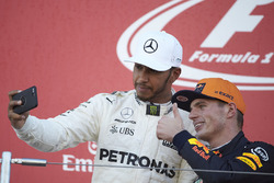 Race winner Lewis Hamilton, Mercedes AMG F1, takes a photo with Max Verstappen, Red Bull, second place, on the podium