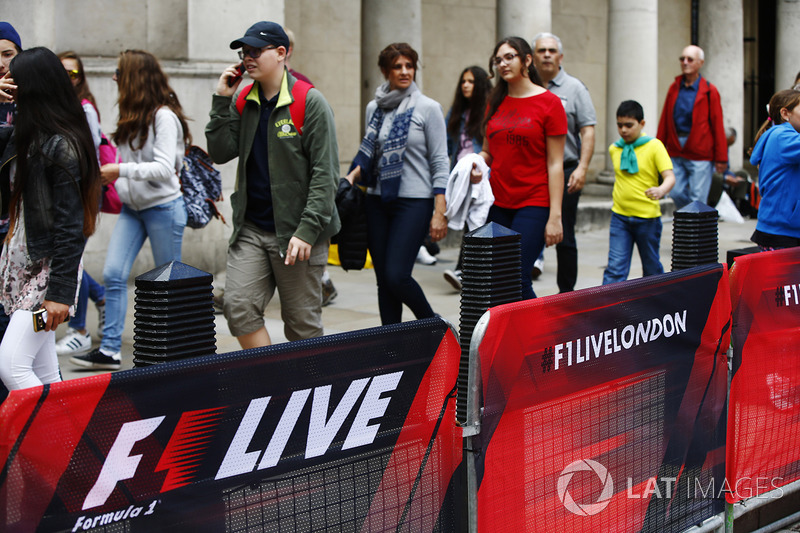 Members of the public walk past railings covered in F1 Live branding