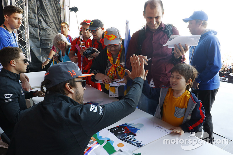 Fernando Alonso, McLaren, give a high-five to a young fan, as Stoffel Vandoorne, McLaren, signs auto
