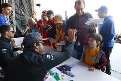 Fernando Alonso, McLaren, dar una palmadita a un joven fan, Stoffel Vandoorne, McLaren, firma autógrafos
