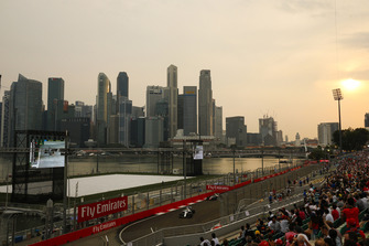 Fans watch Lance Stroll, Williams FW41, leads Kevin Magnussen, Haas F1 Team VF-18, in front of the Singapore skyline