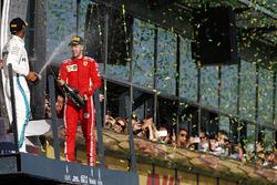 Le deuxième, Lewis Hamilton, Mercedes AMG F1, et le vainqueur Sebastian Vettel, Ferrari, avec du champagne sur le podium
