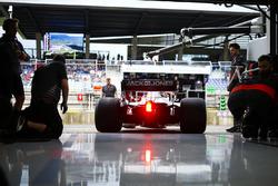 Haas mechanics watch Kevin Magnussen, Haas F1 Team VF-18, exit the team's garage