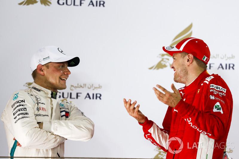 Друге місце Валттері Боттас, Mercedes AMG F1, та перше місце Себастьян Феттель, Ferrari, розмовляють на подіумі