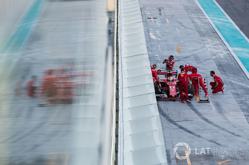 Sebastian Vettel, Ferrari SF70H, is attended to by mechanics in the pit lane