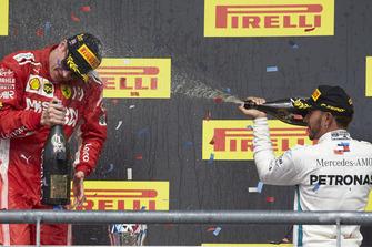 Lewis Hamilton, Mercedes AMG F1, 3rd position, sprays Kimi Raikkonen, Ferrari, 1st position, with Champagne on the podium