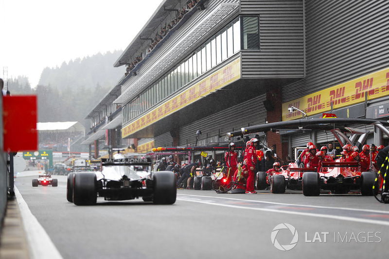Kimi Raikkonen, Ferrari SF71H, and Sebastian Vettel, Ferrari SF71H, make pit stops for intermediate tyres, as Romain Grosjean, Haas F1 Team VF-18, passes by