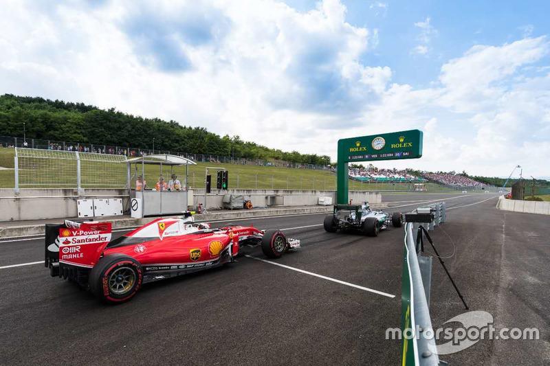 Kimi Raikkonen, Ferrari SF16-H and Nico Rosberg, Mercedes AMG F1 W07 Hybrid exist the pitlane