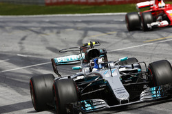Valtteri Bottas, Mercedes AMG F1 W08, raises an arm in victory celebration at the finish, ahead of Sebastian Vettel, Ferrari SF70H