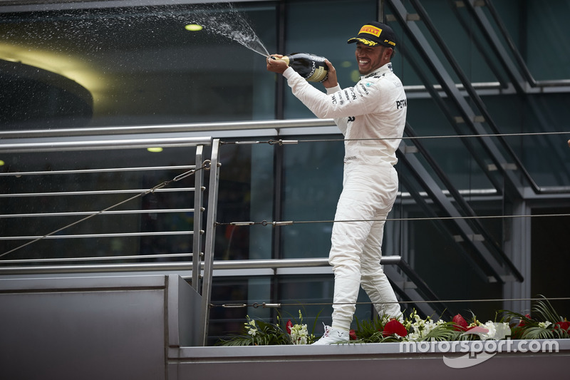 Lewis Hamilton, Mercedes AMG, sprays Champagne from the podium