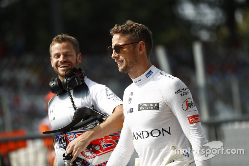 Jenson Button walks in the pit lane with trainer Mike Collier