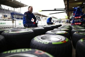 Un mécanicien Toro Rosso travaille sur des pneus Pirelli