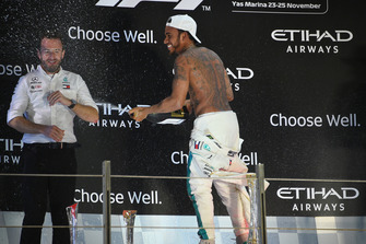 Lewis Hamilton, Mercedes AMG F1 celebrates by spraying the Rose Water at Bradley Lord, Head of Mercedes-Benz Motorsport Communications on the podium